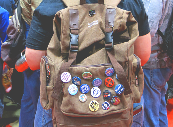 woman wearing comic con buttons on backpack