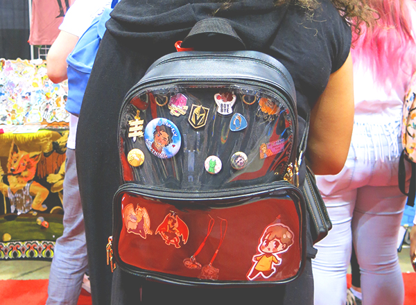 clear backpack displaying comic con buttons