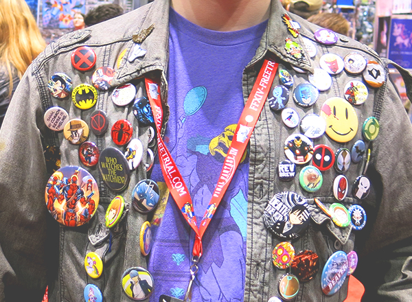 man wearing comic con buttons on jacket