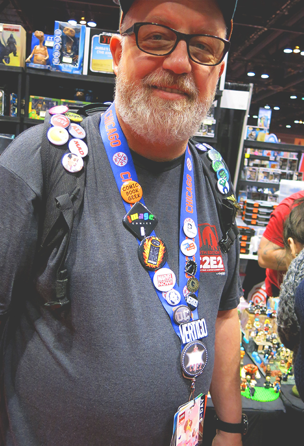 man wearing comic con buttons on backpack